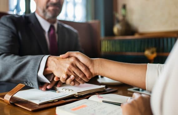 Handshake between man and woman above documents